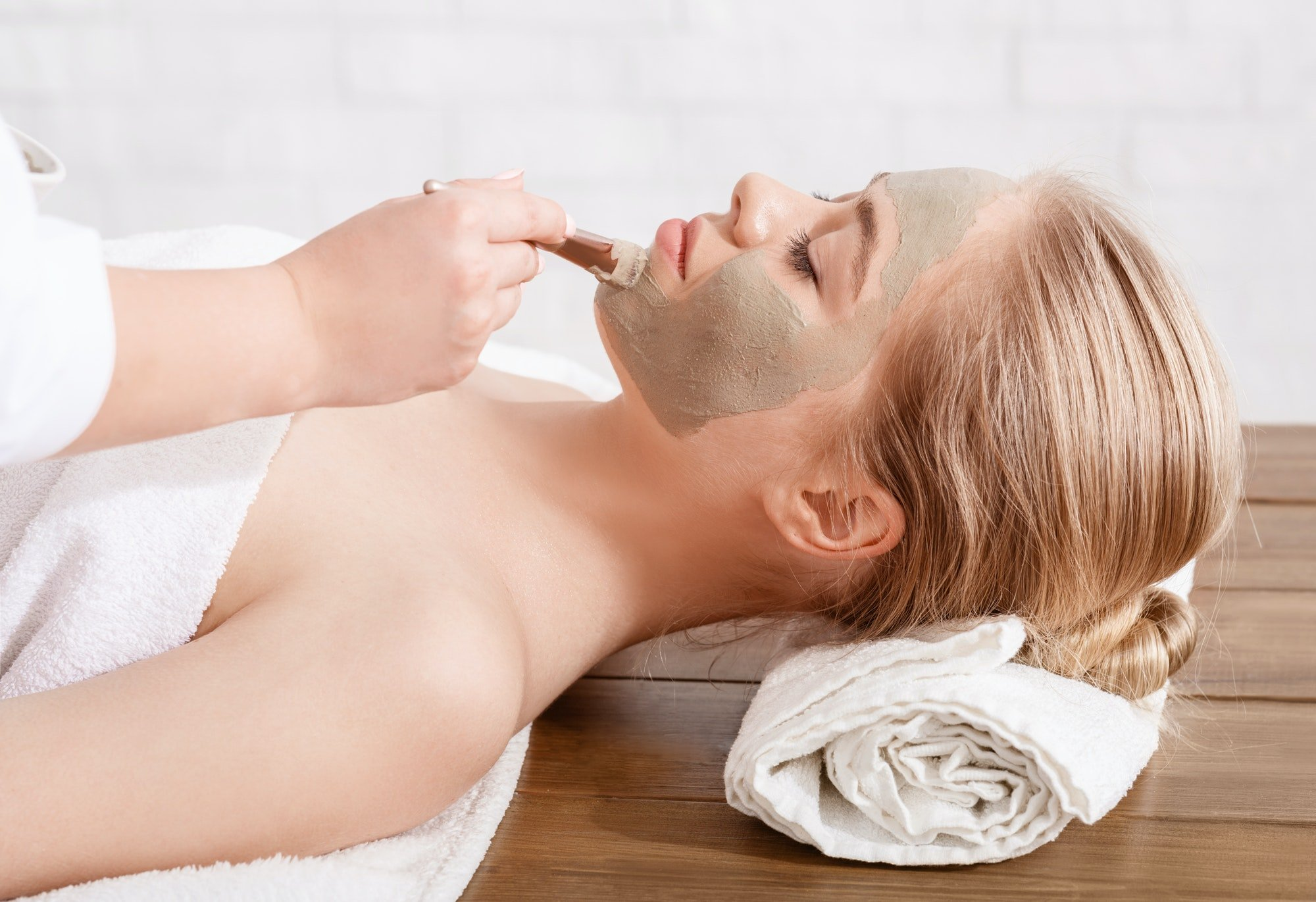 Anti-aging face mask. Beautician applied clay on skin of girl lying on table in spa salon