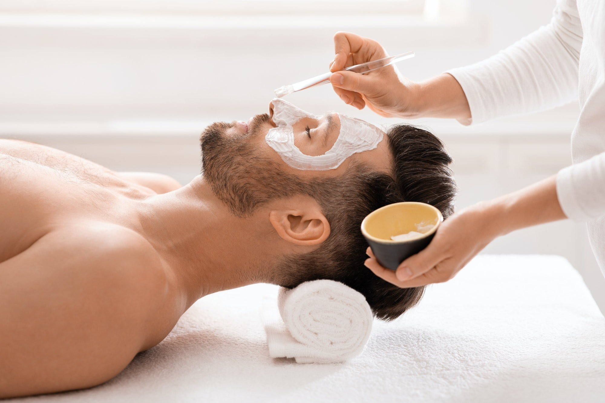 Bearded man getting face treatment at spa salon