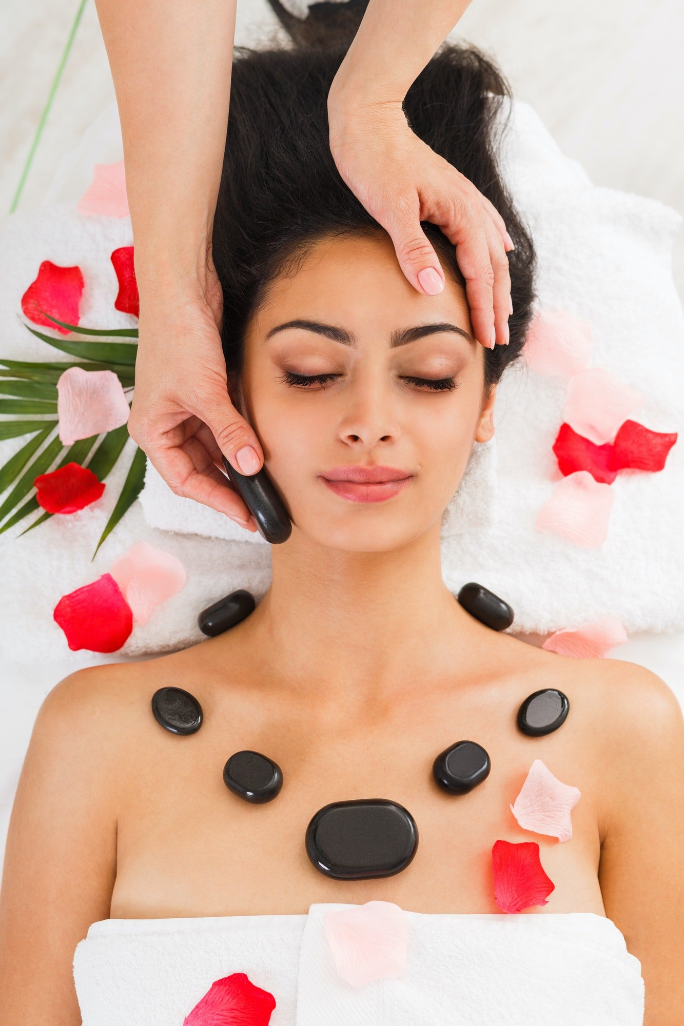 Beautician make stone massage spa for woman at wellness center