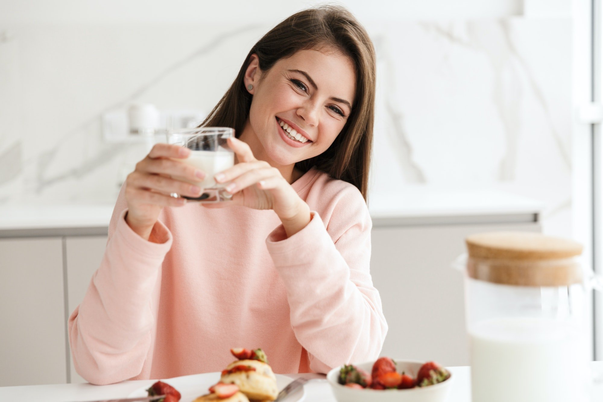 Beautiful smiling young girl having tasty healthy breakfast