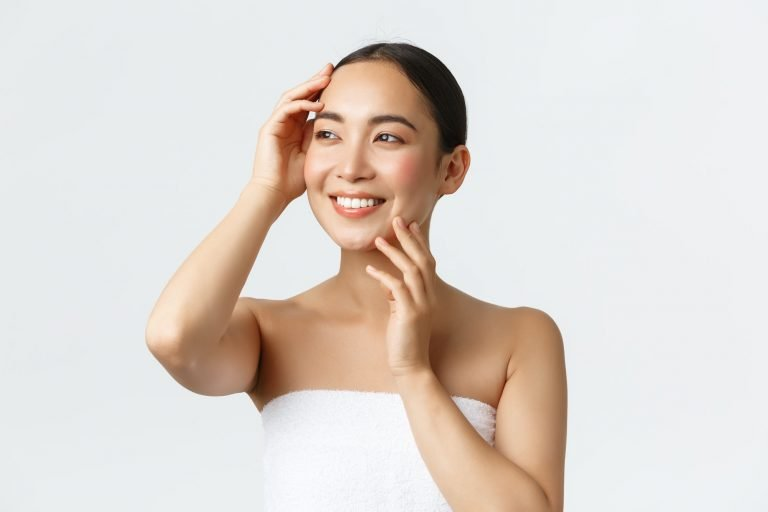 Beautiful tender asian girl in towel looking away pleased, touching clean face, no acne, enjoying