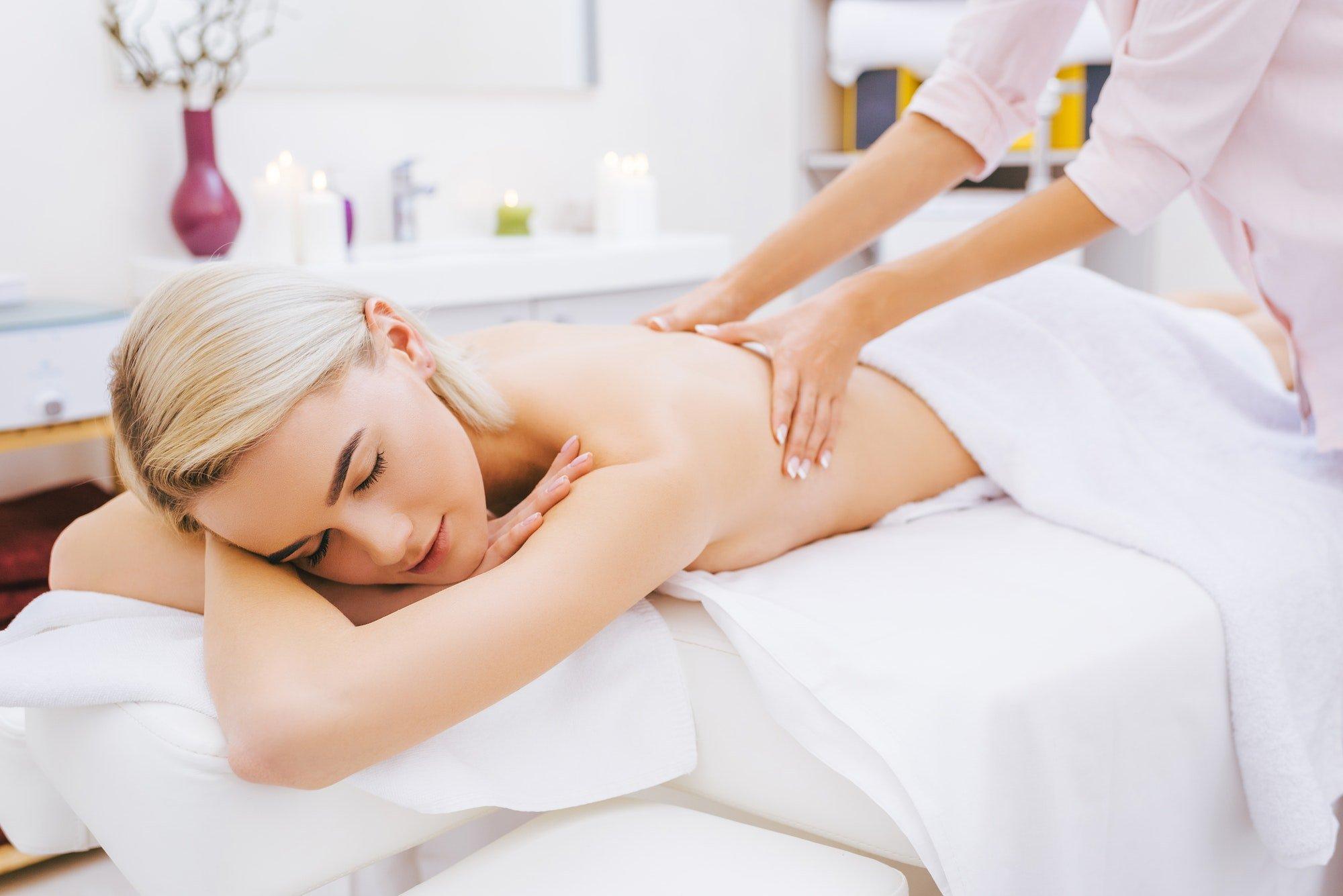 beautiful young woman getting back massage at spa salon