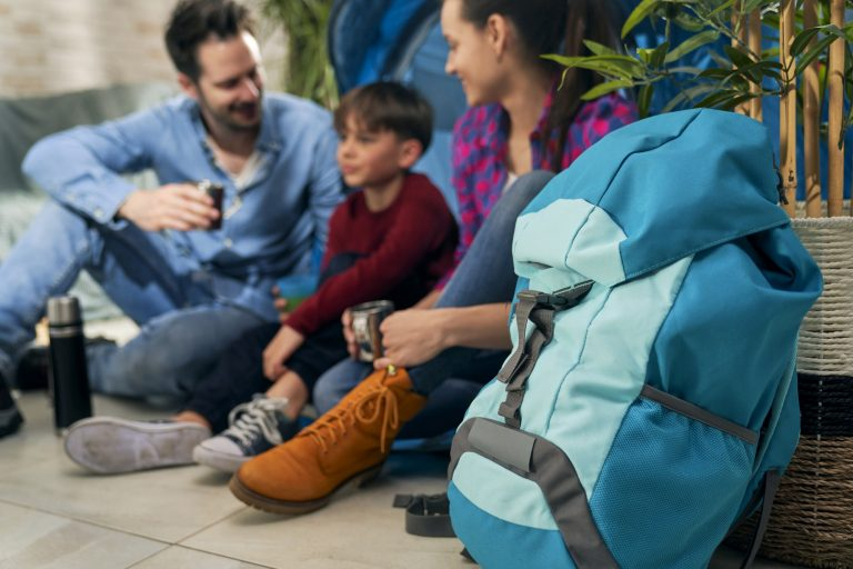 Close up of backpack and family while camping indoors