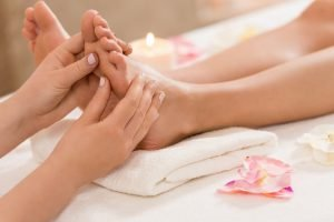 cropped view of massage therapist making feet massage in spa salon