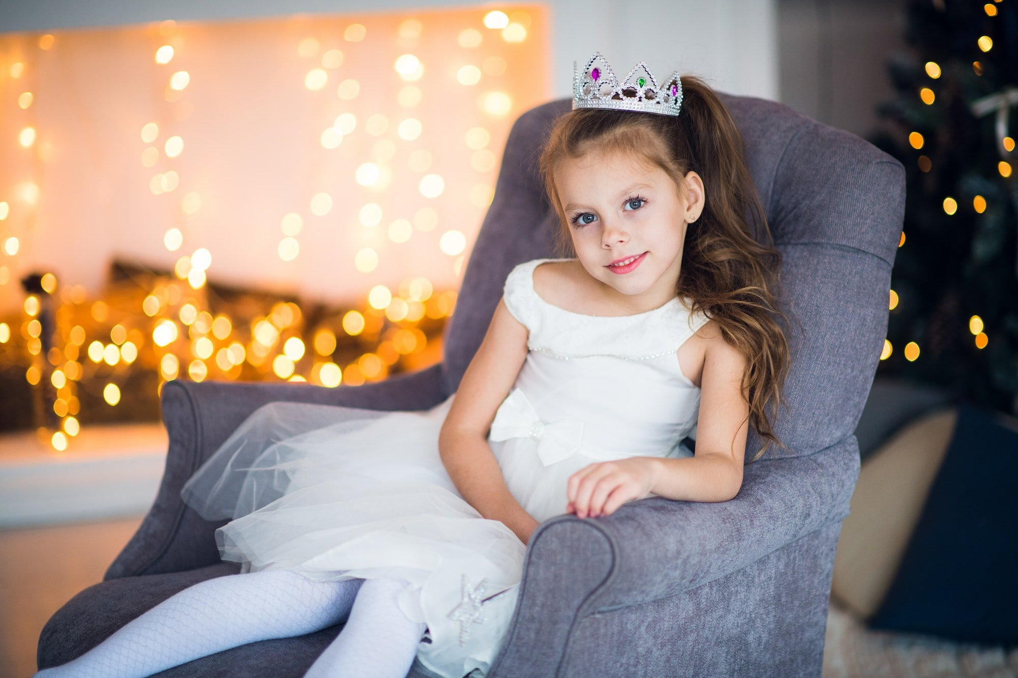 Cute little girl in smart white dress Christmas around the fireplace which decorated with holiday
