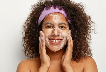 Positive pleasant looking dark haired Afro woman with bare shoulders massages face, washes with soap