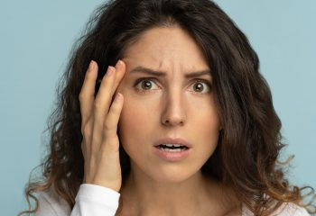Worried woman has signs of aging skin, checking crows feet troubled with wrinkles on face, isolated