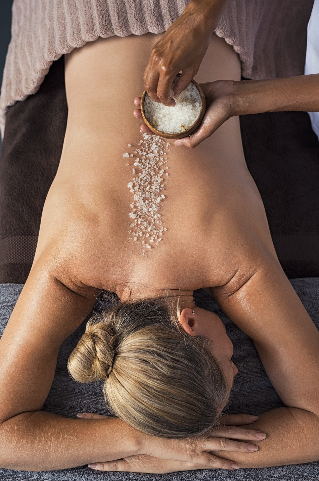 Mature woman enjoying a salt scrub massage at spa