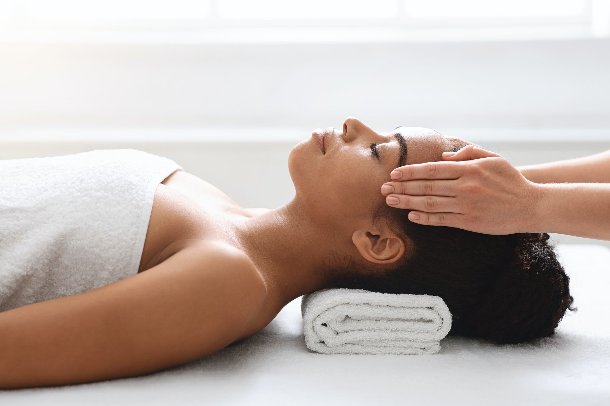 Peaceful african american woman getting healing head massage at spa