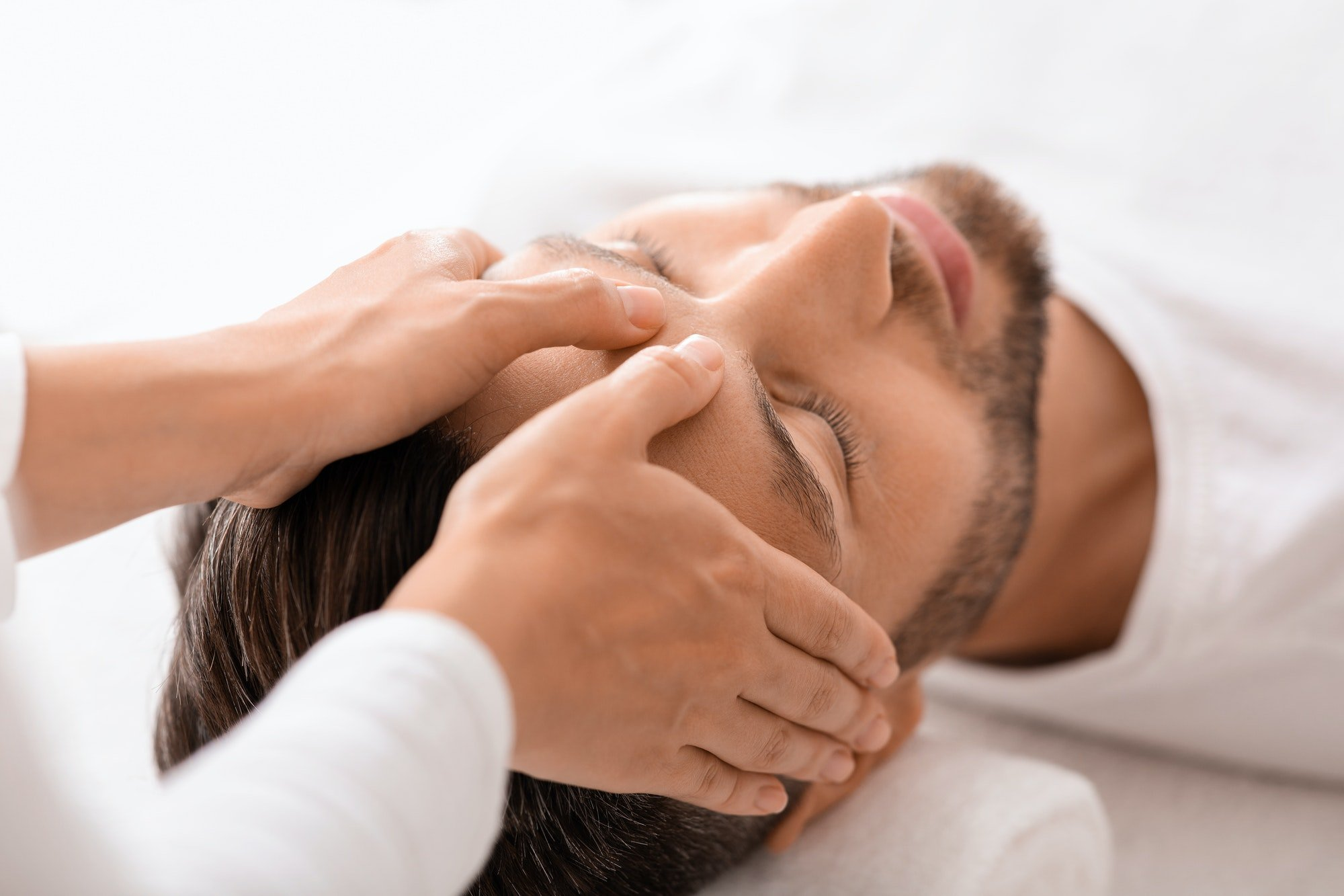 Peaceful man getting healing head massage at spa