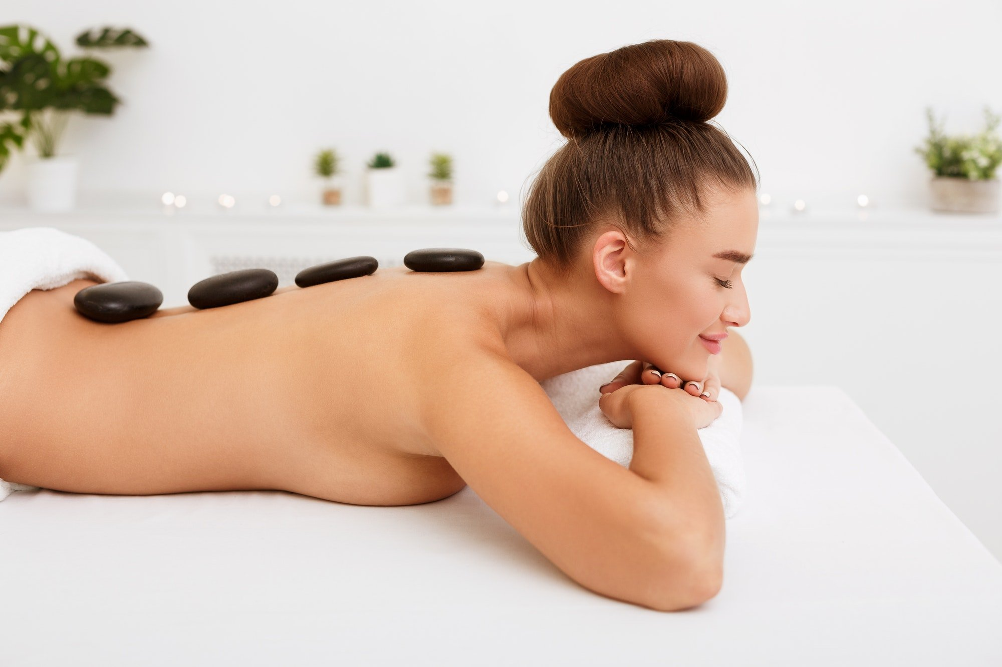 Relaxed woman enjoying hot stone massage in spa