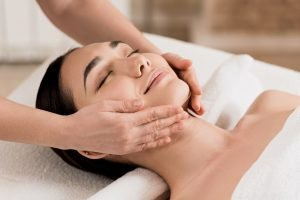 woman getting face massage with closed eyes at spa