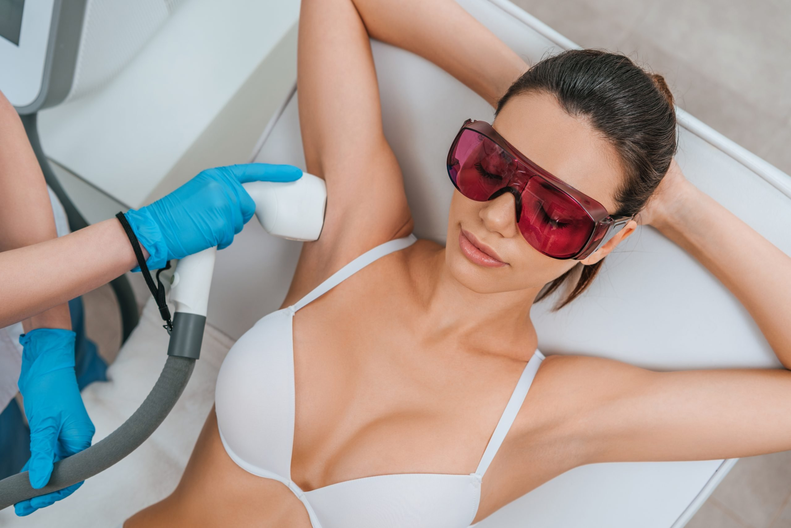 Woman in protective goggles receiving laser hair removal procedure on armpit