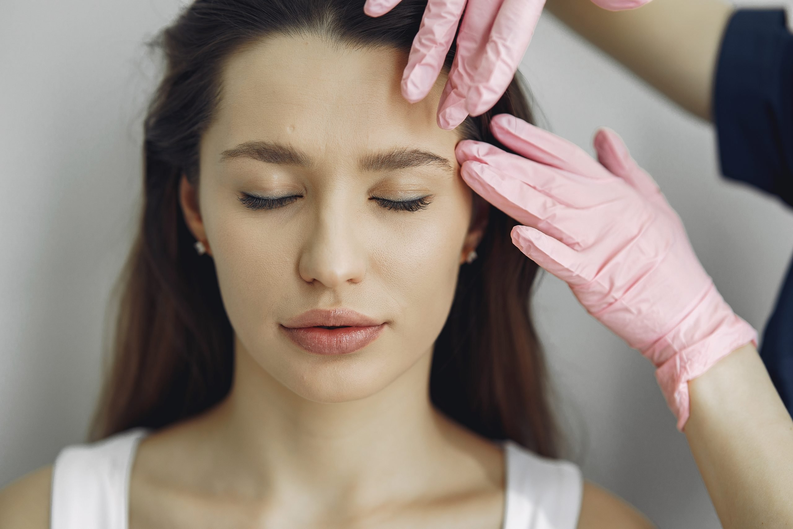 Cosmetologist holds hands near client's face. Woman with cosmetologist. Lady in a beauty studio.