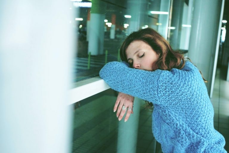 Young woman alone and tired in a bus station