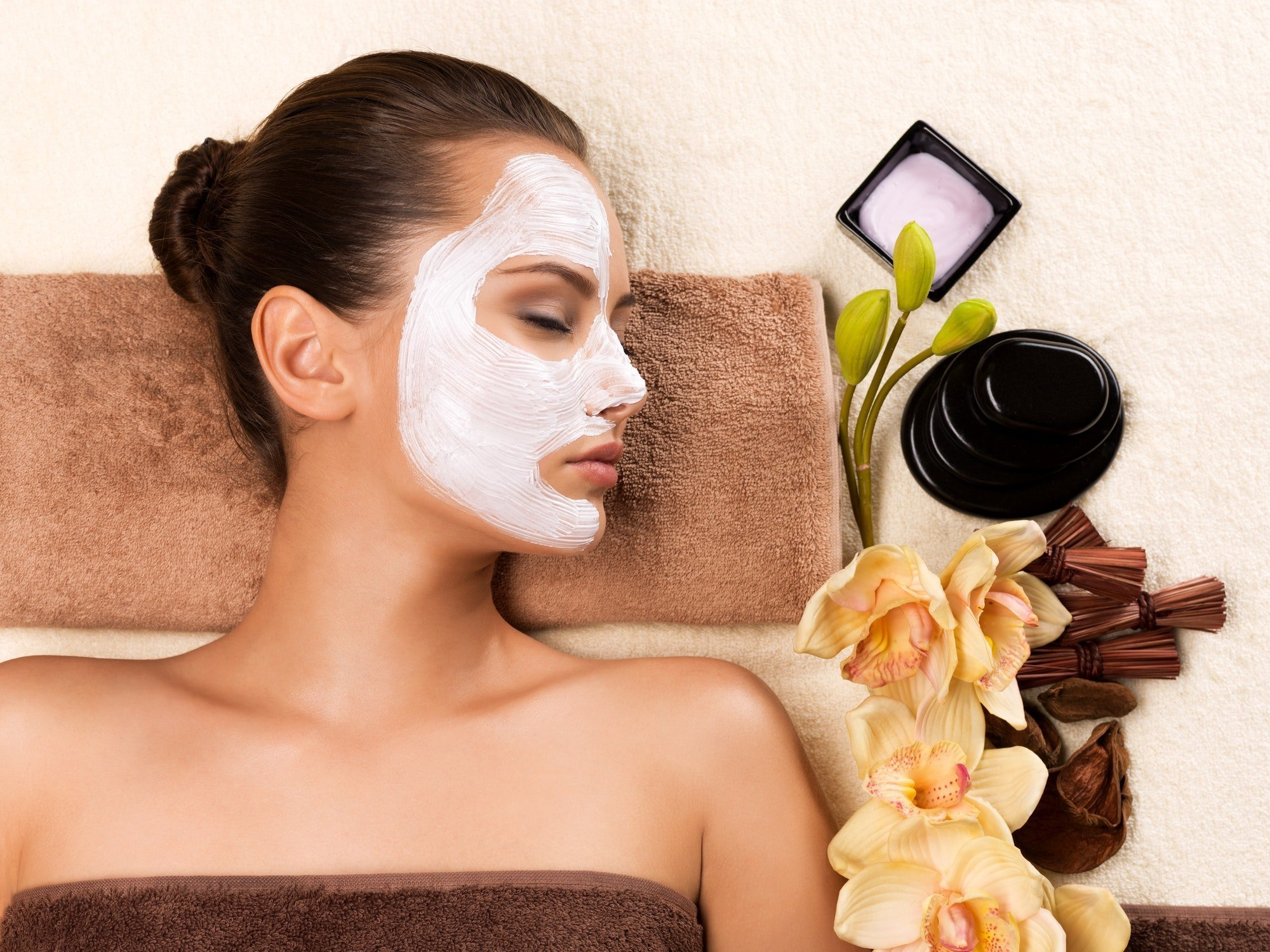 Young woman with mask on her face relaxing in the spa salon.